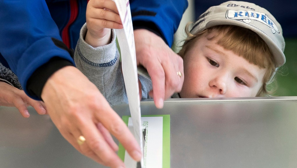 A woman and child cast her ballot during the first round of voting in presidential elections in Vilnius, Lithuania