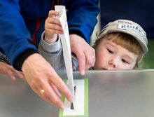 A woman and child cast her ballot during the first round of voting in presidential elections in Viln...