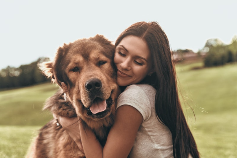 Her best friend. Beautiful young woman keeping eyes closed and smiling while embracing her dog outdoors