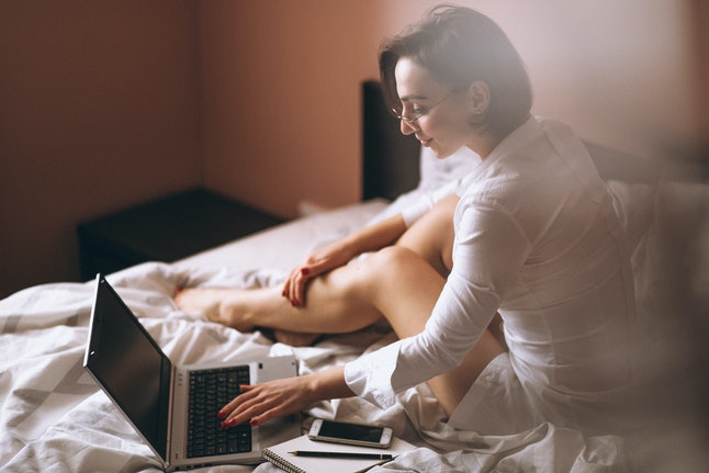 Woman in bed with computer business