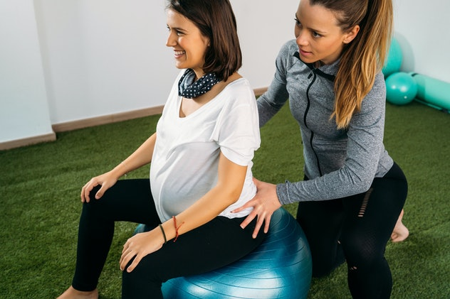 Pregnant woman doing fitness ball and pilates exercise with coach.