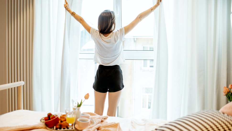 Young woman stretching near the window, having a good morning at the cozy bedroom with breakfast at home or hotel room