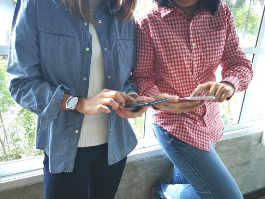 Two women leaning against a window, texting on their phones.
