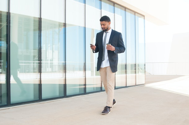 Pensive manager texting message on his way to office. Young black man in formal suit walking near office building, holding cup of coffee and using smartphone. Communication concept