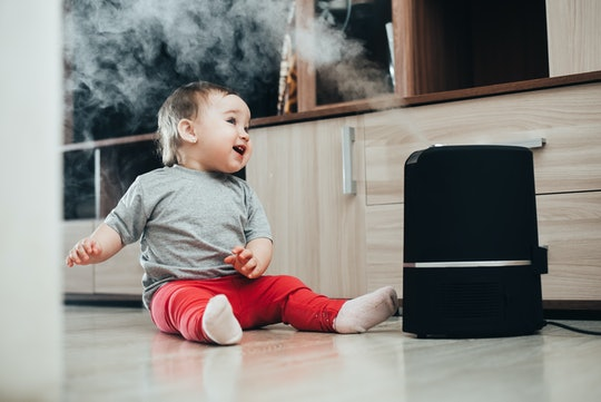 A baby sitting on the floor next to a humidifier