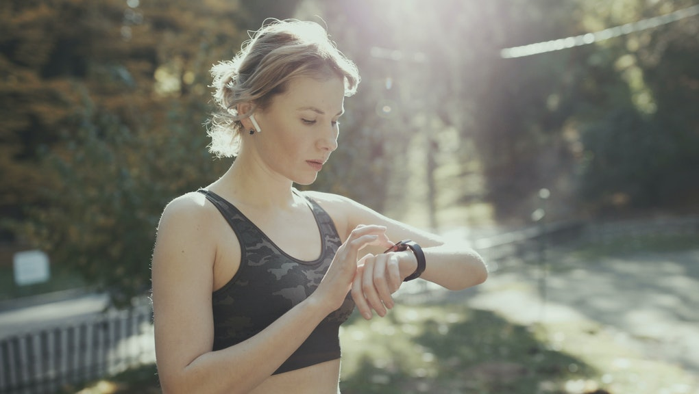 Sport Woman Running In City Park Wearing Smartwatch And Wireless Earphones