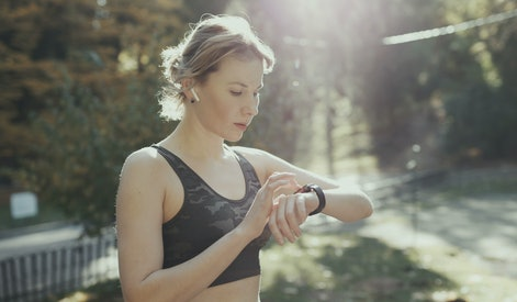 Sport Woman Running In City Park Wearing Smartwatch And Wireless Earphones