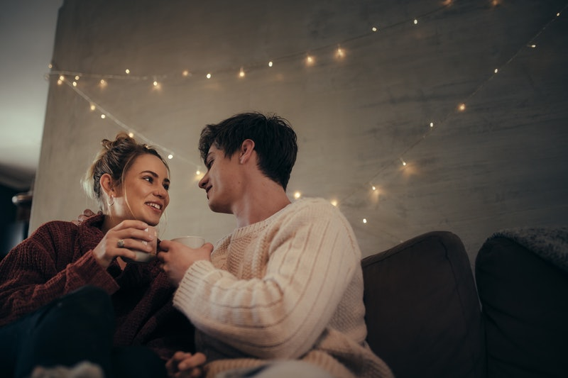Cozy couple sitting on sofa and having coffee together. Man and woman relaxing on couch drinking coffee.