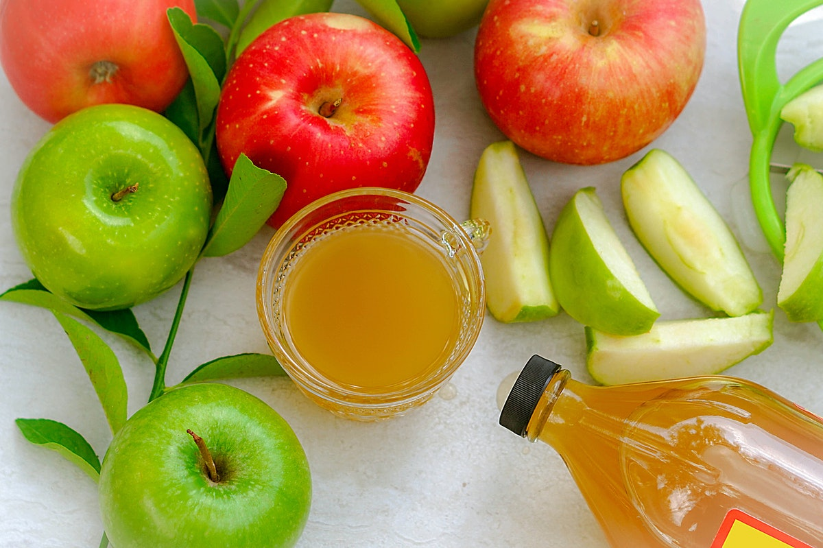 Apple cider vinegar in a glass cup in the middle of red and green apples with the bottle near by. Dr...