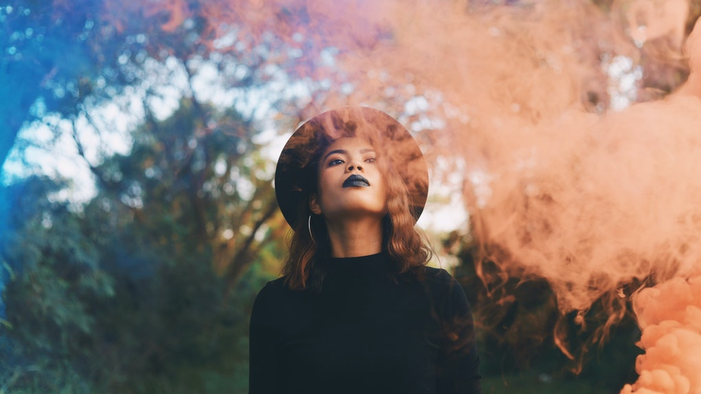 Beautiful woman in black dress standing in forest in Halloween concept.