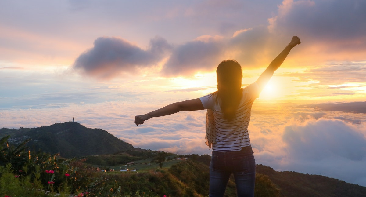 Women standing in the morning on top of the mountain with the sunrise.
