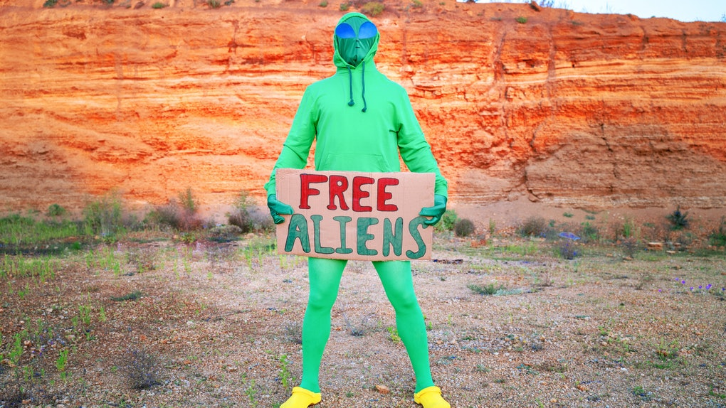 "a man dressed in a green alien carnival costume suit at a lone rally with a sign ""free aliens"" on the background of a desert canyon"