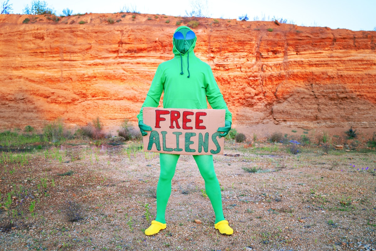 """a man dressed in a green alien carnival costume suit at a lone rally with a sign """"free aliens"""" on th..."""