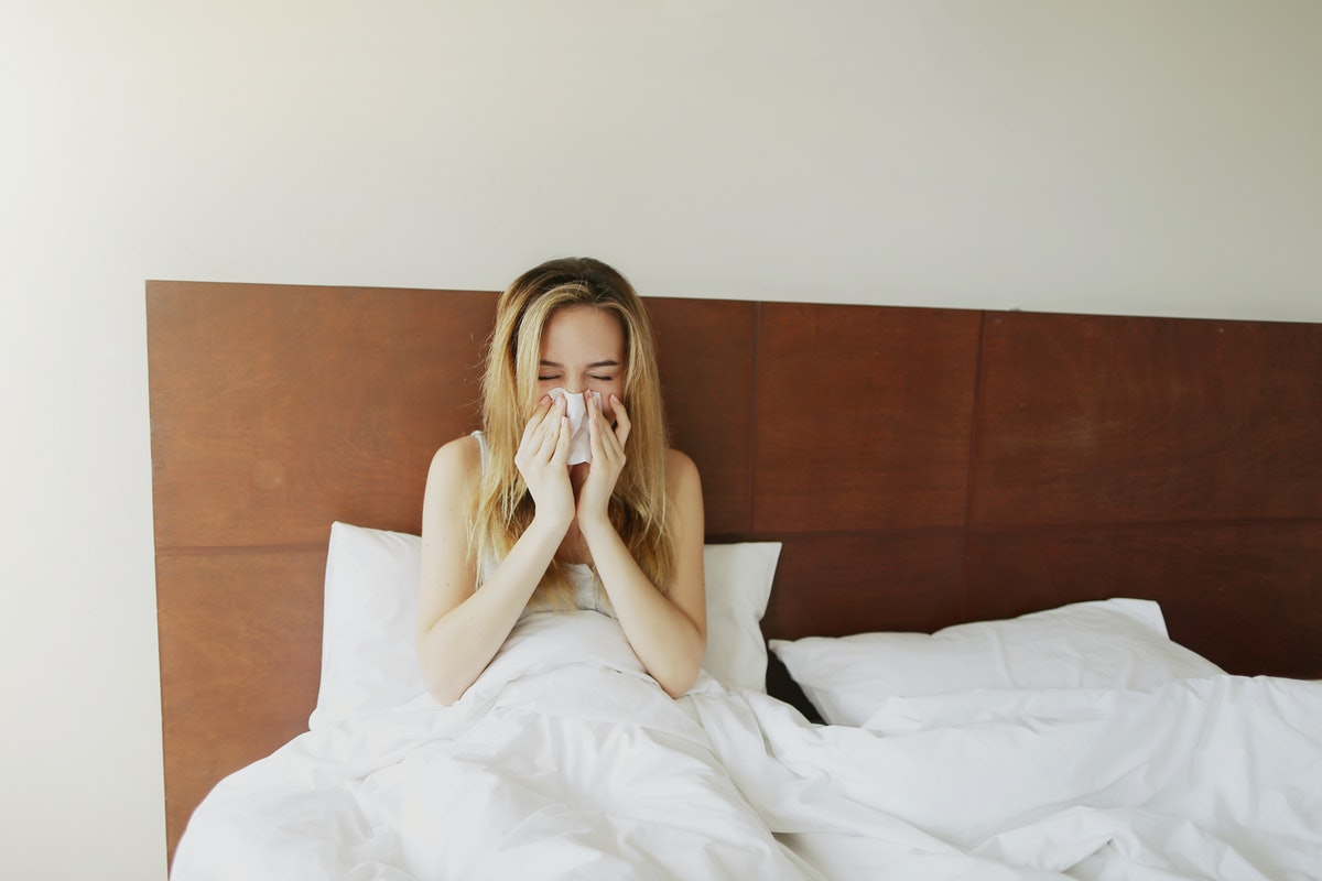 Female sick Woman sneezes in white bed with napkin Sunlight , get cold outside. Concept of pills med...