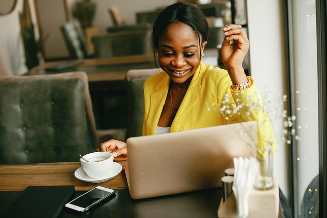 Elegant black woman. Lady in a yellow jacket. Businesswoman working in a office