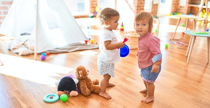 Adorable toddlers playing around lots of toys at kindergarten