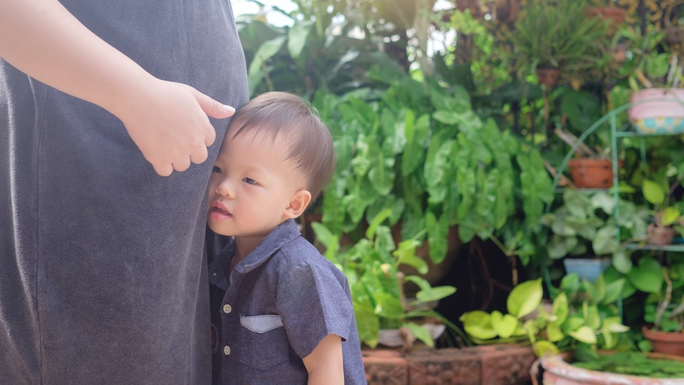 A toddler boy leans up against his pregnant mom's belly