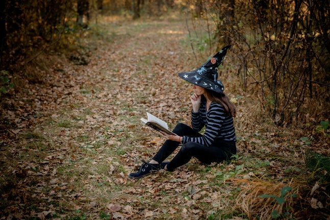 Halloween witch in the woods reads a book in the woods