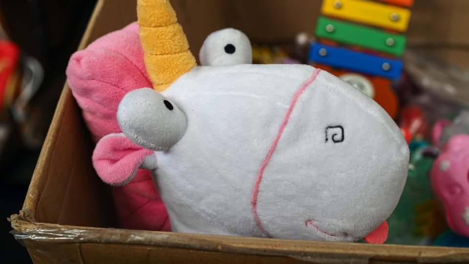 Flea market. Cardboard box with second-hand toys, the head of a unicorn plush in the foreground.