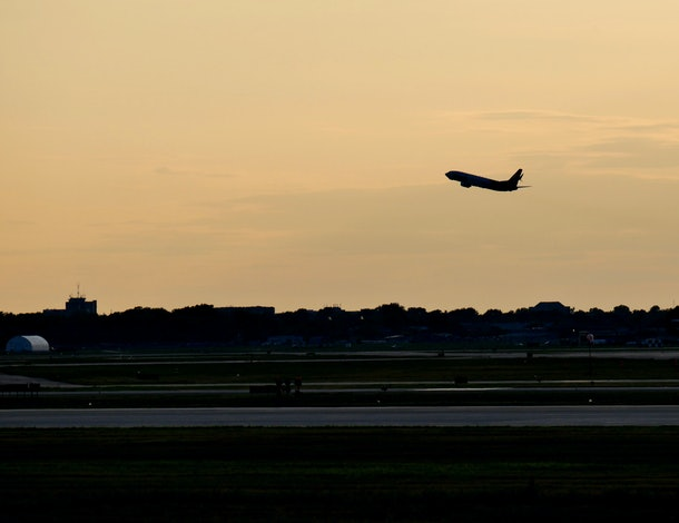 A plane taking off into the sunset