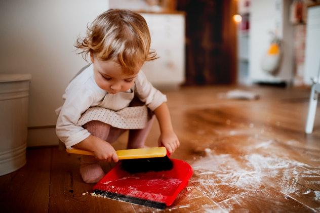 A small toddler girl with brush and dustpan sweeping floor in the kitchen at home.