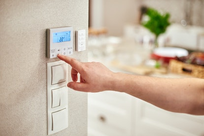 hand adjusting temperature inside house