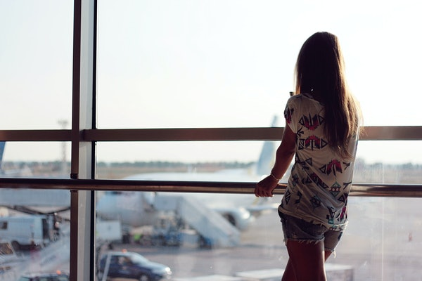 A young woman looks out at planes from an airport window. The chances of a plane crash are extremely low.