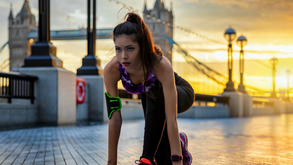 Pretty female athelete in starting position ready to do her workout during sunrise in an urban city