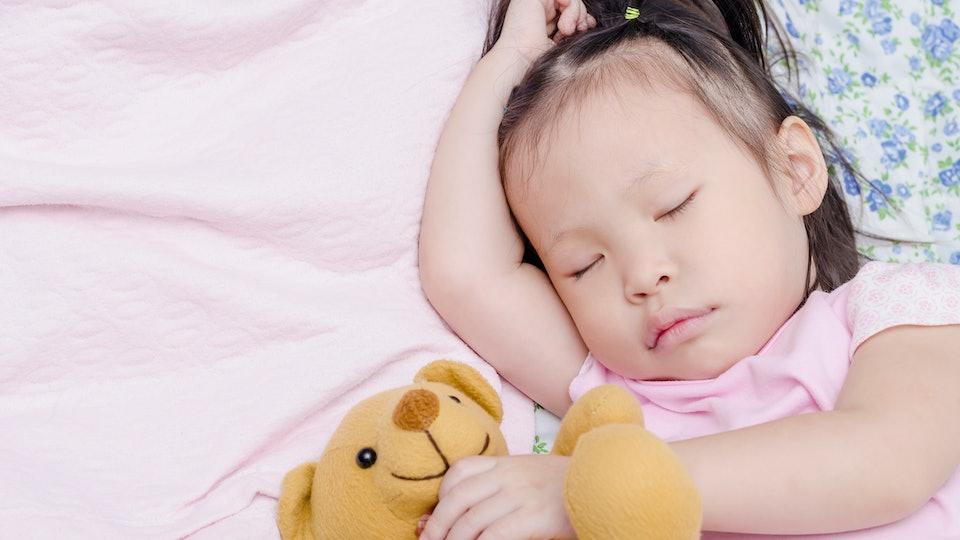 Little Asian girl sleeping on bed