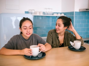 Teen sisters talking while they are having breakfast in the kitchen