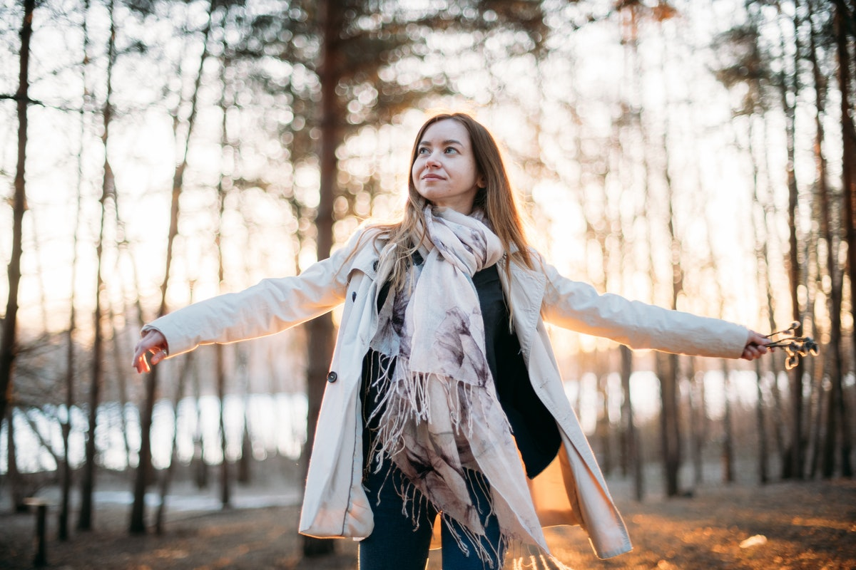 The girl cheerfully turns in the rays of the setting sun. A young woman in a light raincoat is danci...