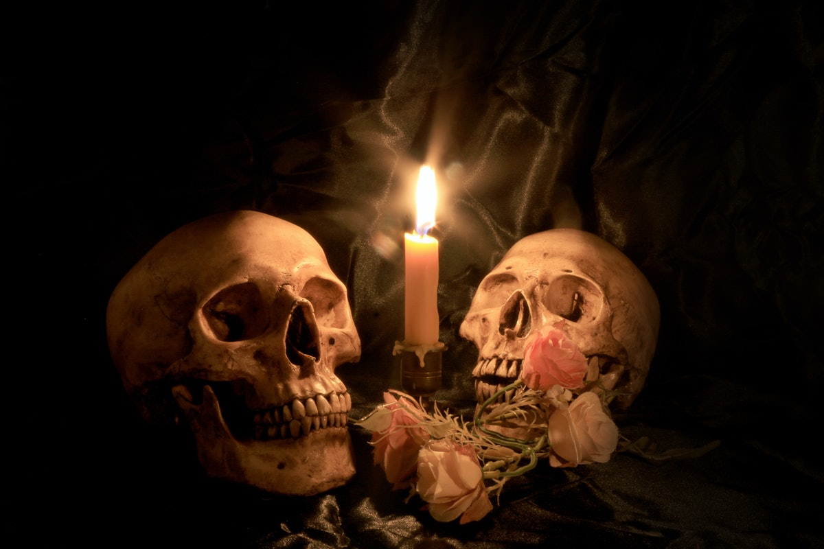 Two Human Skulls and dry flowers with light candle in dim valentines night on old wooden table / Still life Image