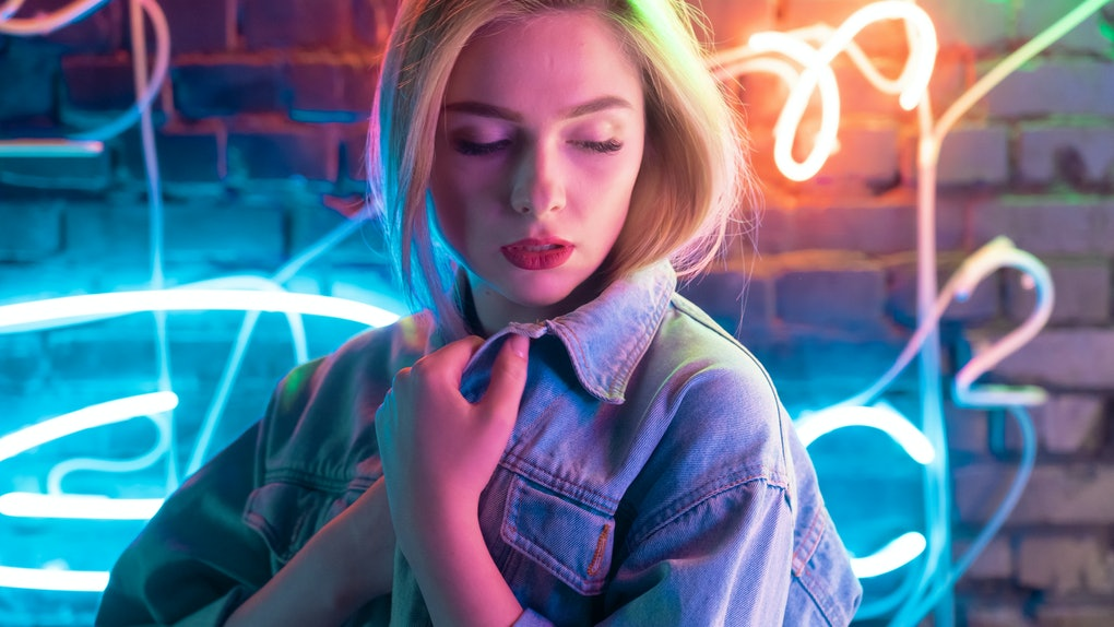 Attractive young woman wearing stylish trendy denim jacket standing near brick wall illuminated with blue orange neon light, pretty fashion girl in modern cloth night club glow nightlife style