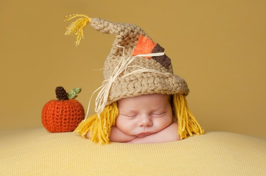 Four week old newborn baby boy wearing a crocheted scarecrow hat. He is sleeping on a gold blanket next to a crocheted pumpkin.