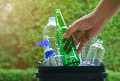 Close up hand dropping plastic and glass bottle into the bin for separating recycle materials from t...