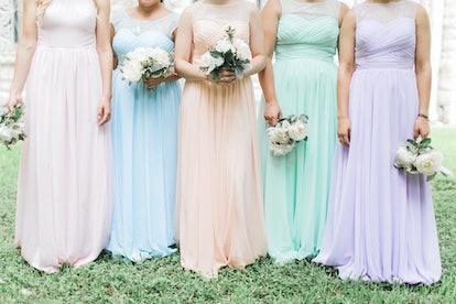 pastel bridesmaids dresses, bridesmaids holding bouquets, pink, peach, blue, mint and purple gowns