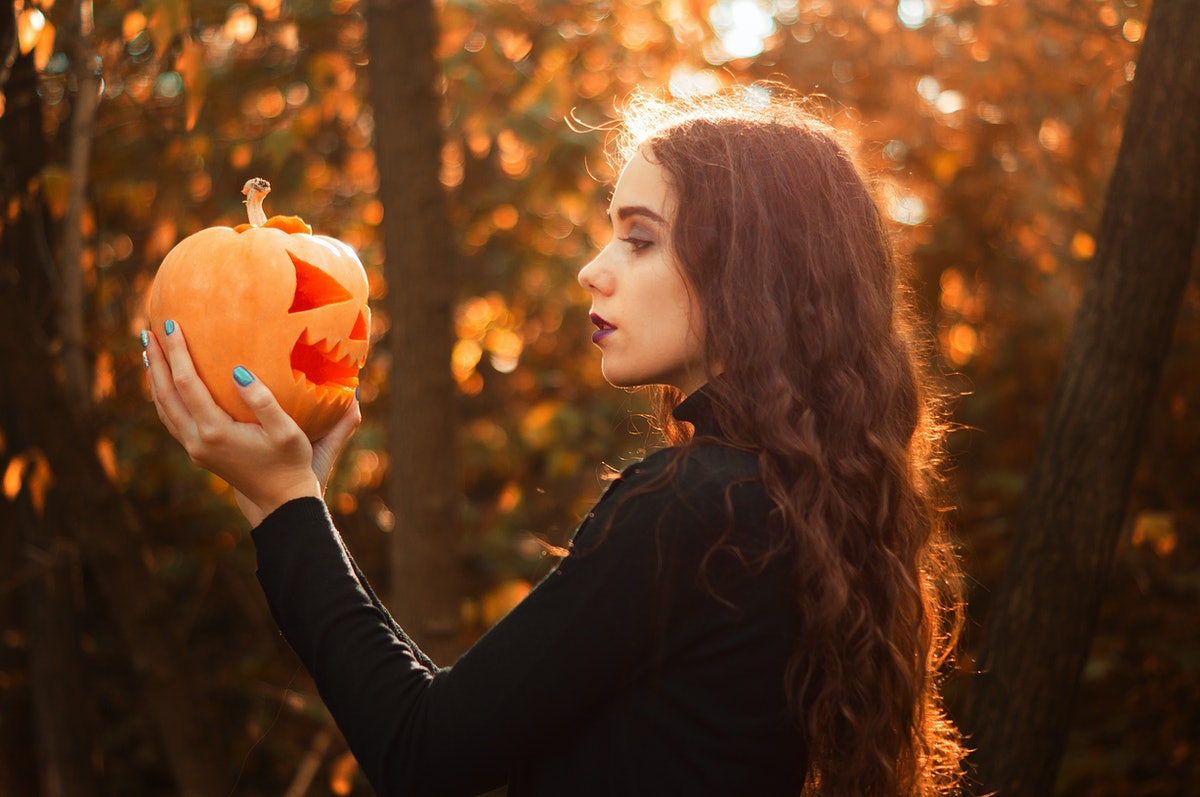 Beautiful girl in a witch costume holds a jack lantern