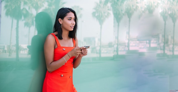 Attractive young woman in casual wear looking around while waiting for phone call from operator, millennial Latin hipster girl with cell smartphone gadget spending leisure time for exploring city