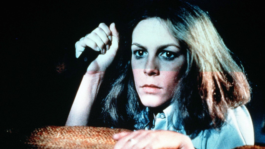 'Halloween'  Film - 1978 -    Laurie Strode (Jamie Lee Curtis) looking over the top of a sofa with a knife in her right hand.