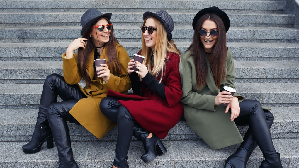 Stylish girls with unusual makeup in trendy coats, scarves, hats and leather shoes on the stairs to the galley drink coffee