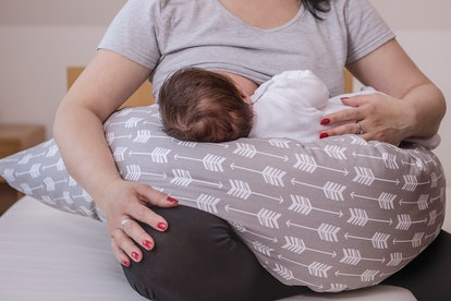 mother breastfeeding baby on support cushion