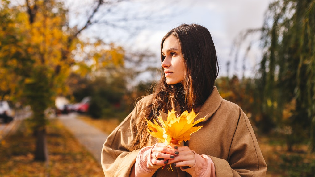 Cheerful sad girl with long brown hair wearing autumn beige coat, walking at the park. Autumn walk. Woman portrait. Dreaming girl holding leaves bouquet. Woman enjoying fall nature. Leaves bouquet.