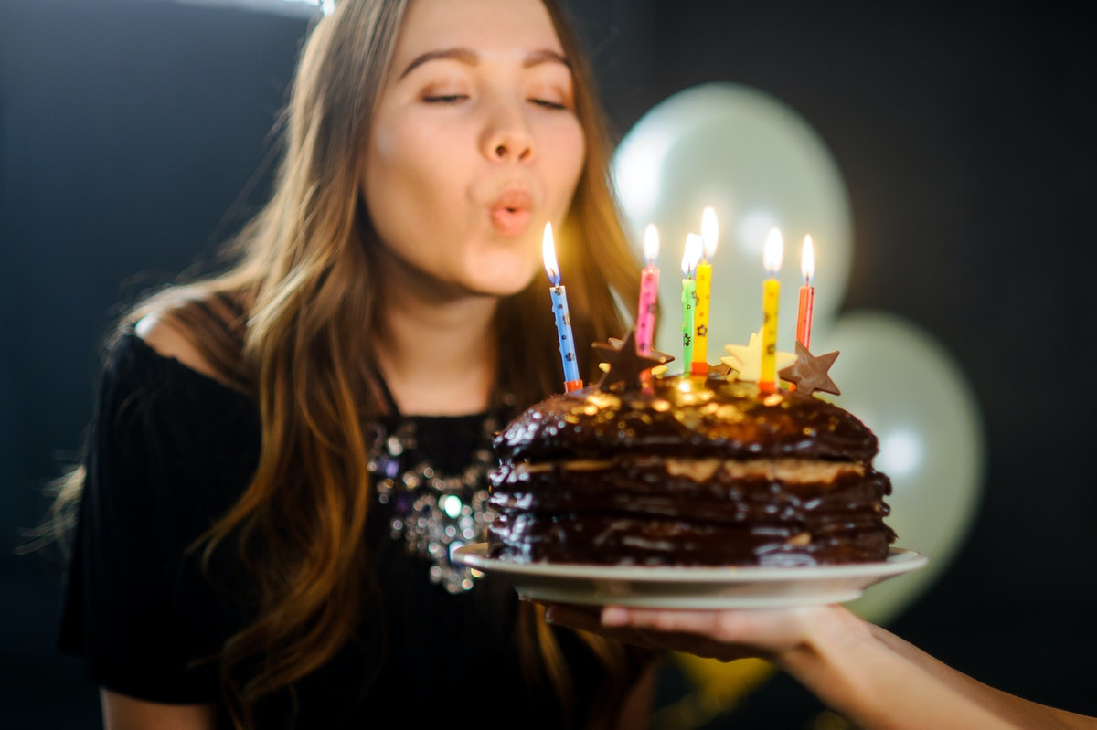 Charming girl blows out the candles on birthday cake. The birthday girl is elegantly dressed. She makes a wish. Happy Birthday.