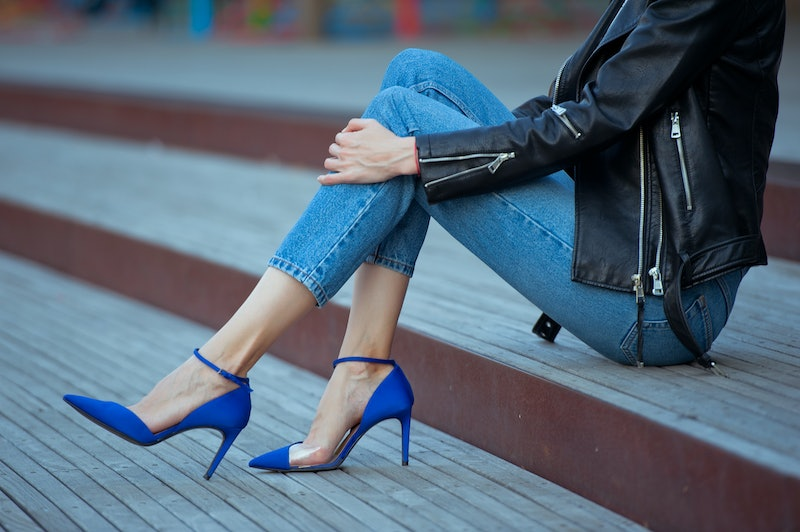 Fashionable young woman wearing high heel blue shoes, white t-shirt, jeans and black leather jacket. Street style.