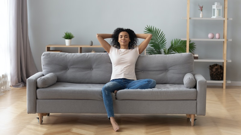 Woman on a couch meditating and practicing mindfulness.