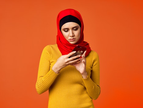 muslim woman looking into the phone
