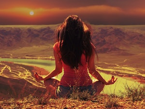 Portrait of young caucasian beautiful sport  women sitting at lotus pose at sunset background of river in red shirt and blue pants