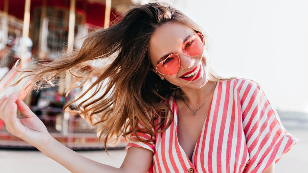 A happy woman in a striped shirt and red sunglasses poses in the sunshine.