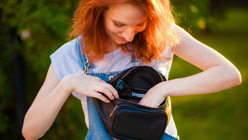 A red-haired girl looks through her black fanny pack that has multiple zippers, which makes it one of the best fanny packs for Disney days.