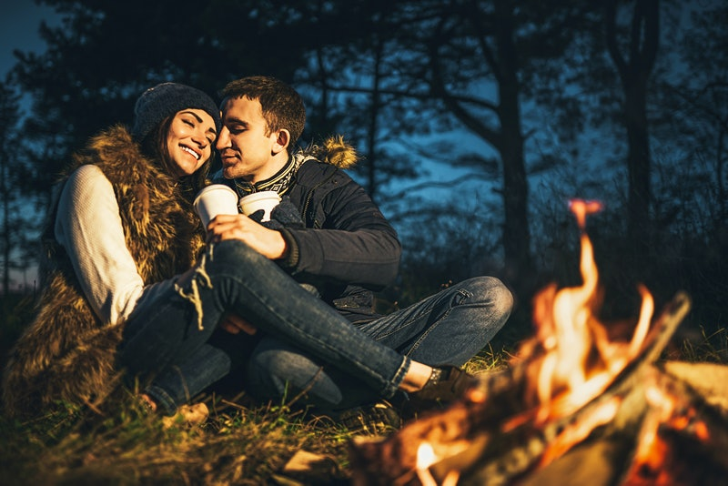 Pretty young couple drinking hot beverage in the forest near bonfire